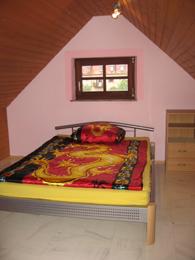Ausschnitt des Zimmers 'Perls' mit Bett, Schrank und Fenster